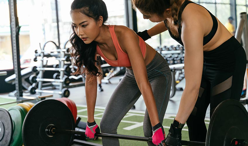 Woman lifting weights with fitness trainer