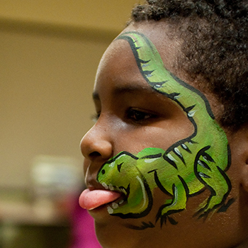 Little Boy With His Face Painted Like A Dinosaur
