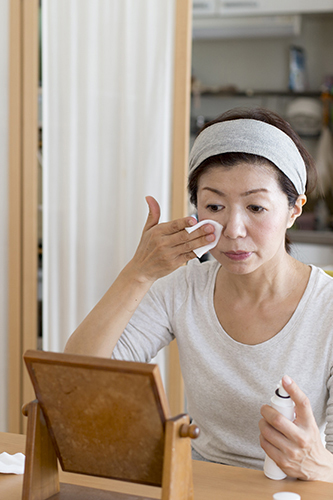 Woman applying skincare at home